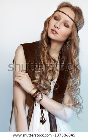 Bohemian woman in spring and summer clothes with beautiful accessories, natural make-up and shiny hairstyle. Fashion hippie style. Long curly hair. - stock photo
