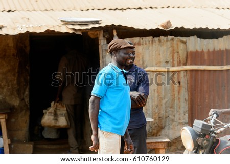 BOHICON, BENIN - JAN 12, 2017: Unidentified Beninese man in blue shirt and a cap smiles at the local market. Benin people suffer of poverty due to the bad economy.