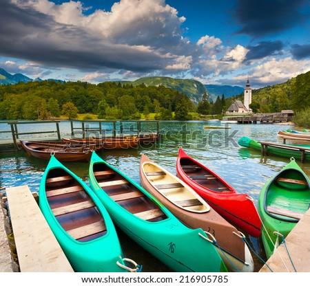 Bohinj Lake with boats and Church of St John the Baptist, Triglav National Park, Slovenia. - stock photo