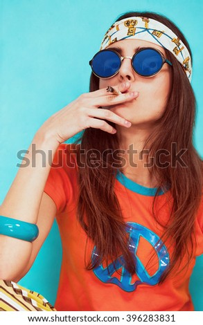 Boho girl portrait smoking weed and wearing sunglasses