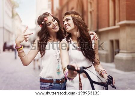Boho girls walking alley of city  - stock photo
