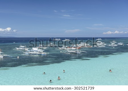 Bohol, Philippines - Jun 1, 2015: Swimmers and Banca boats on Alona Beach in Panglao Island, Bohol. Aloha beach is the most visited tourist spot  in Bohol.  - stock photo