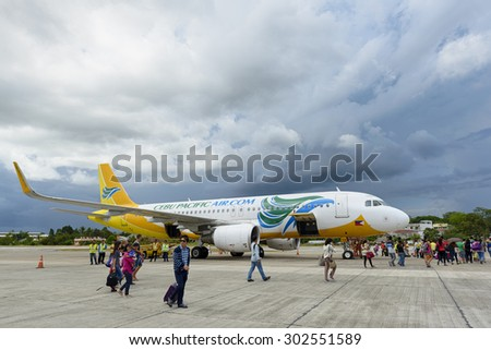 Bohol, Philippines - Jun 1, 2015: Tourists  getting on of a Cebu Pacific Air plane on Tagbilaran Airport on Bohol island, Philippines. Bohol Island is a popular tourist destination.   - stock photo