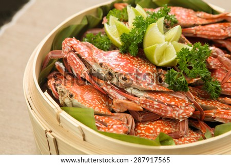 Boiled blue swimming crabs with lemon on bamboo steam pot,close up view - stock photo
