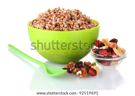 Boiled buckwheat in a green bowl isolated on white