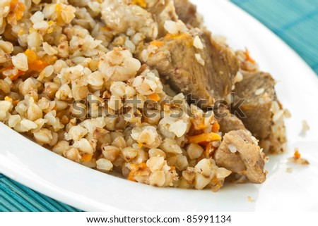 Boiled buckwheat porridge with meat on white plate