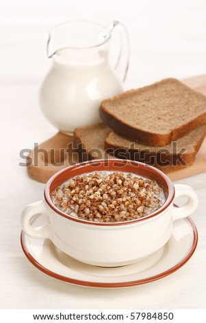 Boiled buckwheat with milk on served table on white background