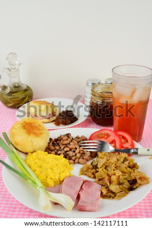 Boiled Cabbage, fried ham, black eyed peas and creamed corn soul food plate with green onions and sliced tomato.  Side plate of buttered biscuit and fig preserves with ice cold glass of sweet tea. - stock photo