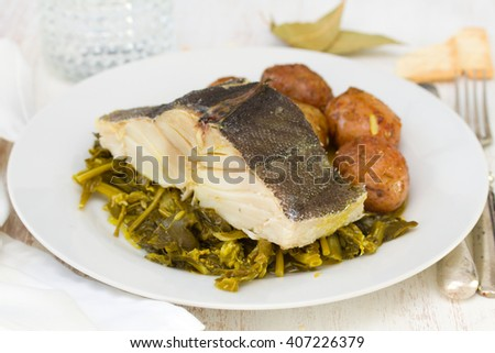 boiled cod fish with potato and greens on white plate on white wooden background - stock photo