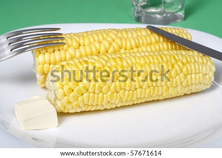 boiled corn cob with butter lying on a plate, set on the table - stock photo