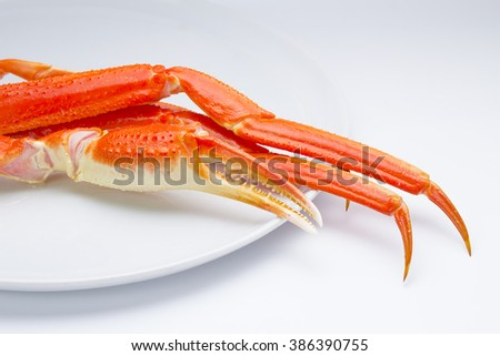 Boiled crab claws on a plate over white background - stock photo