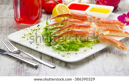 Boiled crab claws with sauce , lemon and cherry tomatoe with tasty drink over wooden background - stock photo