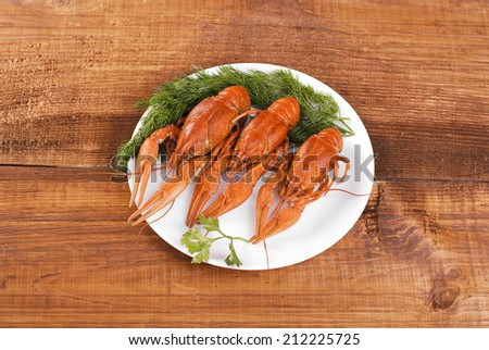 boiled crawfish on a plate with greens - stock photo
