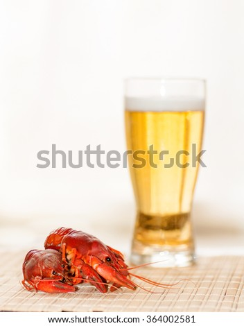 boiled crayfish on the background of a glass of beer - stock photo