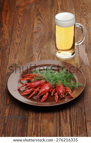 boiled crayfish on wooden surface with a beer and dill. old style plate - stock photo