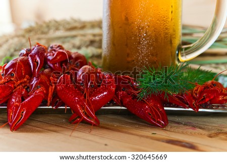 boiled crayfish with herbs on wooden table - stock photo