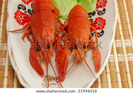 Boiled crayfishs and lettuce on plate - stock photo