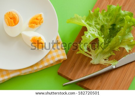 Boiled egg and salad leaves - stock photo