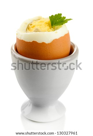 Boiled egg in egg cup, isolated on white - stock photo