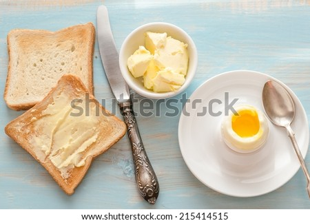 Boiled egg with crispy toasts on the wooden table - stock photo