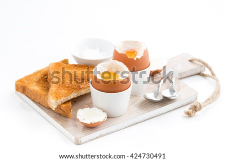 boiled eggs and crispy toasts on a wooden board, horizontal - stock photo