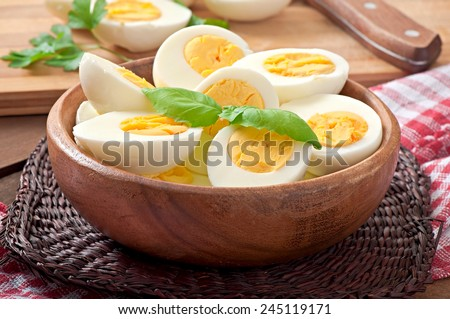 Boiled eggs in a bowl decorated with parsley leaves - stock photo