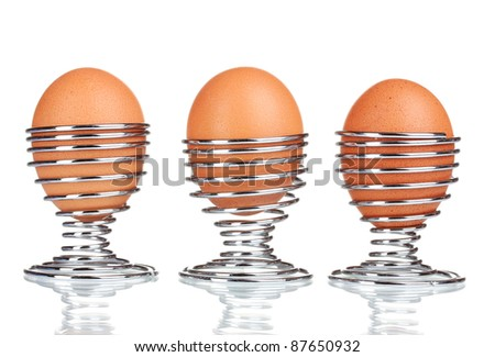 boiled eggs in metal stands isolated on white