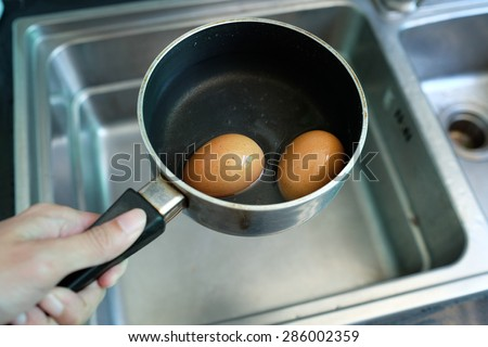 Boiled eggs in water. - stock photo