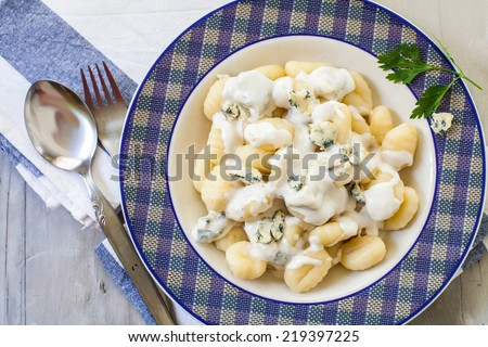 Boiled gnocchi with blue danish cream on plate - stock photo