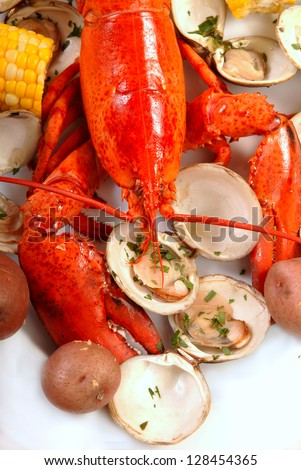 Boiled lobster dinner with clams, corn and potatoes - stock photo