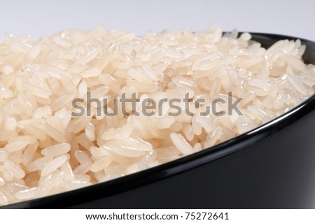 boiled long grain rice in a black bowl close-up on white background - stock photo