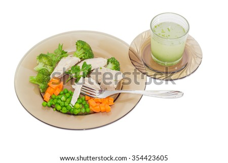 Boiled meat with boiled green peas, broccoli, carrot on a dark glass dish, fork and meat broth with herbs in glass on a light background