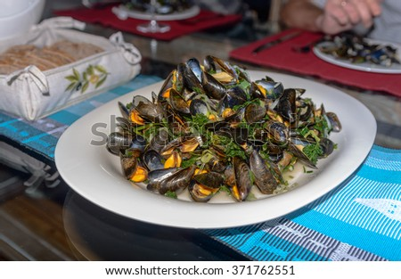 Boiled mussels in a cooking dish on a on table. Selective focus - stock photo