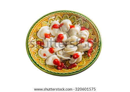 boiled pelmeni filled with ketchup on a ceramic plate a white background