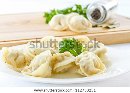 Boiled pelmeni in a bowl with spices on a light background - stock photo
