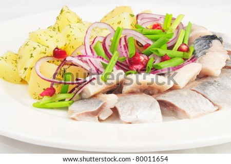 Boiled potato with a herring and an onions - stock photo