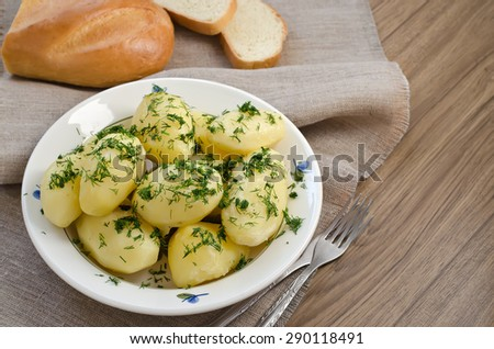 Boiled potatoes in a white bowl with dill and bread. The cup stands on beige napkin. - stock photo