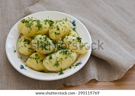 Boiled potatoes in a white bowl with dill. The cup stands on beige napkin. - stock photo