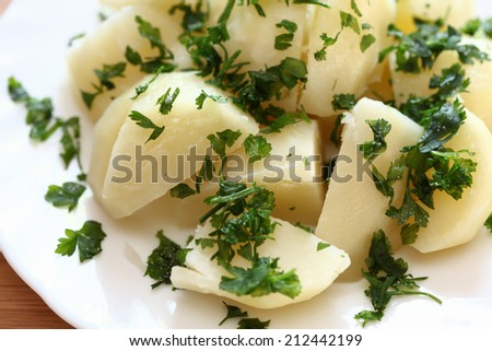 Boiled potatoes with parsley on a plate. Close-up. - stock photo