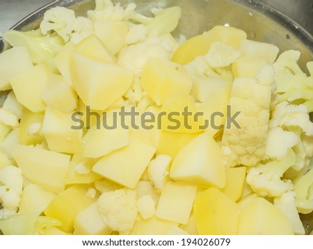 Boiled potatos and cauliflowers mixed in metal strainer. - stock photo