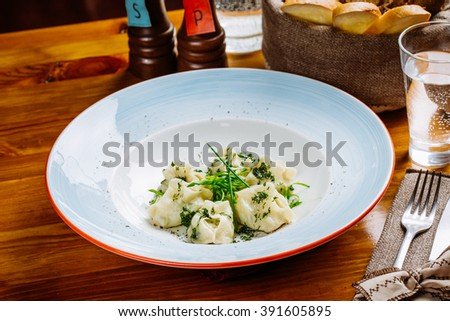 Boiled prepared homemade russian dumplings or pelmeni with beef meat on the plate with fresh parsley and black pepper.diet, cooking, culinary and food concept. - stock photo