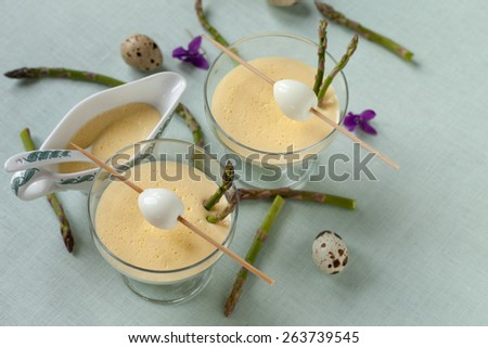 Boiled quail eggs served with steamed asparagus and mustard mayonnaise. - stock photo