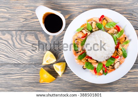 Boiled Rice and seafood - mussels, shrimps, baby spinach leaves, pieces of chili peppers on a white dish  on a wooden background,  soy sauce  in a gravy boat and lemon slices. top view - stock photo