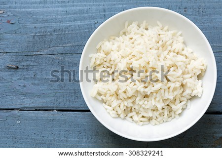 Boiled rice in a white china bowl on a rustic blue wooden table, copy space in the background - stock photo