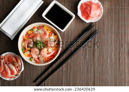 Boiled rice with shrimps and vegetables on bamboo mat background - stock photo