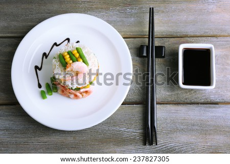 Boiled rice with shrimps and vegetables on plate, on on wooden background - stock photo