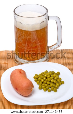 Boiled sausage with canned green peas on a white plate and big mug of beer  - stock photo