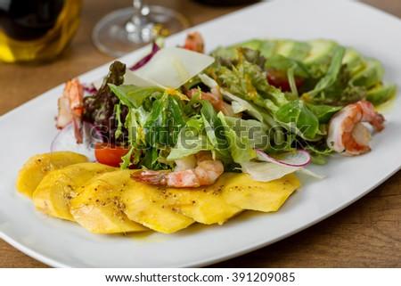 boiled shrimp, pineapple, avocado, lettuce, arugula, tomatoes and radishes on a white plate - stock photo