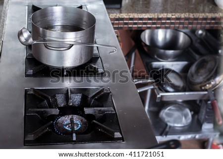 Boiled soup pot on gas stove in busy kitchen - stock photo