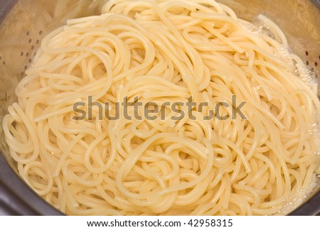 Boiled spaghetti in a collander.